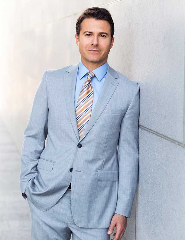 corporate portrait of man lawyer in grey suit leaning against wall outdoors