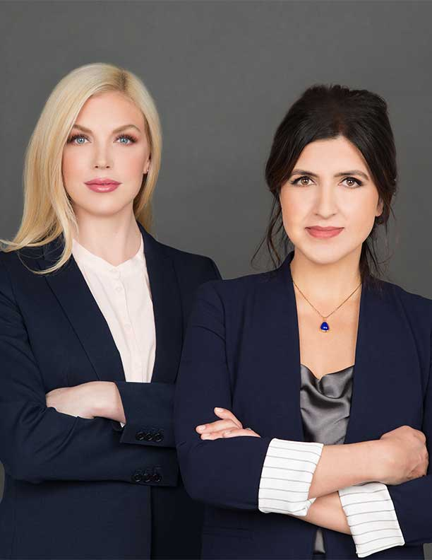 power photograph of 2 female lawyers together with folded arms and smiles in studio Irvine CA